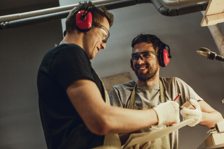 Craftsmen smiling and making sketches together