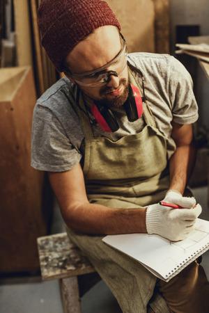 Craftsman with sketchbook looking away
