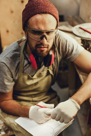 Thoughtful craftsman making sketches Stock Photo