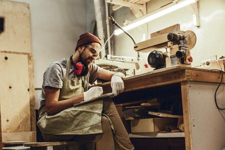 Craftsman making sketches near workbench Stock fotó - 115949874