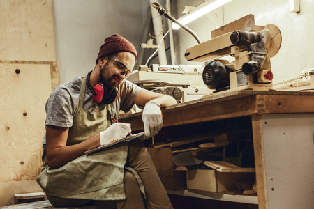 Smiling craftsman drawing near workbench Stock Photo