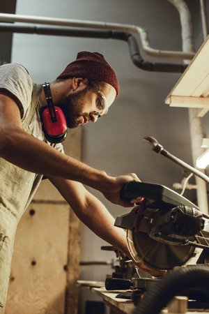 Bearded man working with circular saw in workshop