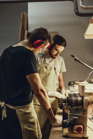 Young man looking at colleague working in joinery