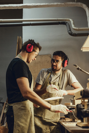 Smiling carpenters discussing sketch