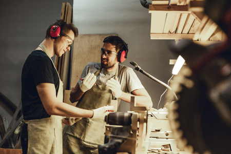 Young carpenters speaking near workbench