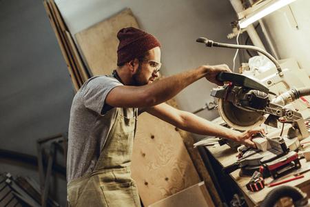 Carpenter cutting wood in workshop Imagens - 115953455