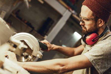 Man in goggles using circular saw Imagens - 115953457