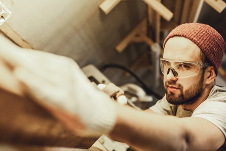 Handsome carpenter straightening piece of wood Imagens - 115953460