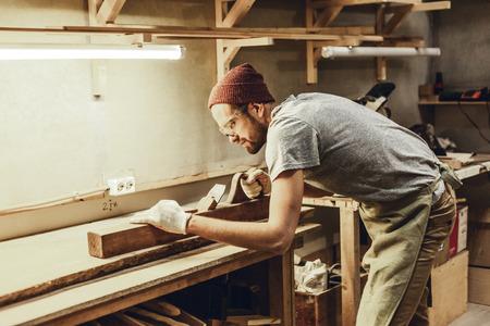 Professional carpenter straightening plank Standard-Bild
