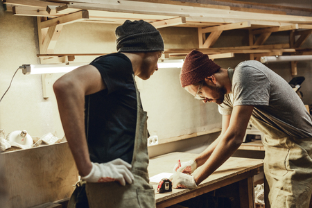 Two carpenters making sketches on workbench Stock Photo