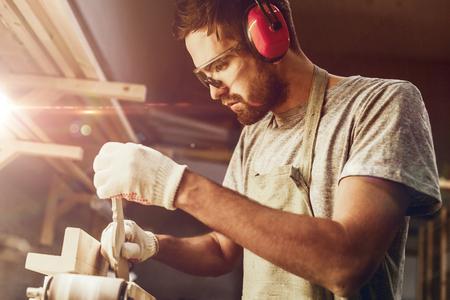 Brodaty rzemieślnik kształtujący drewniany detal na szlifierce taśmowej
