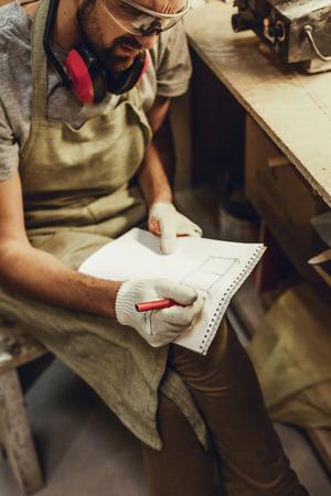 Crop craftsman sketching in notebook