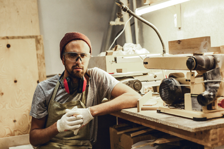 Serious carpenter sitting near equipment