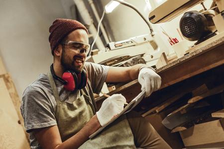Smiling craftsman sketching near workbench