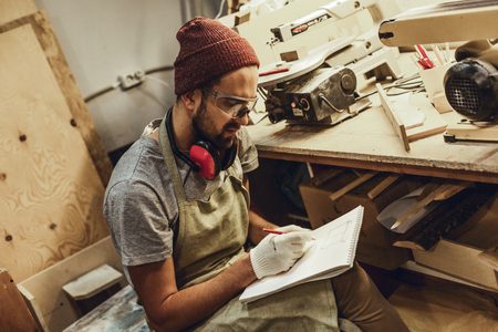 Young craftsman sketching in workshop Stock Photo