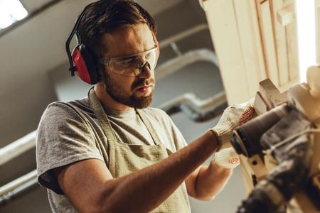 Focused carpenter working on belt sander