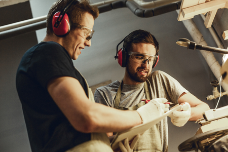 Cheerful craftsmen drawing in sketchbook together Stock Photo
