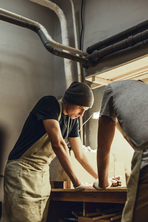 Two craftsmen standing near workbench