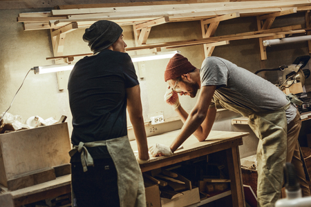 Two carpenters working in workshop