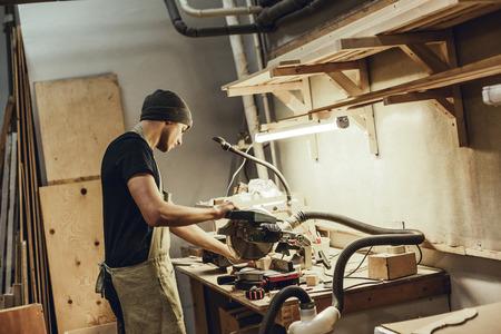 Young craftsman using circular saw near lamp Standard-Bild