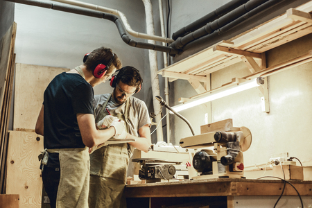 Young craftsmen drafting near workbench Stock Photo