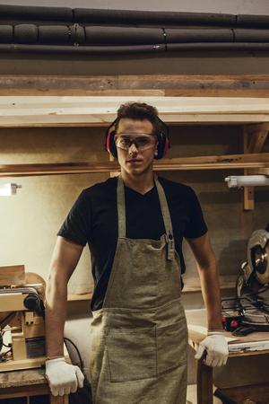 Confident carpenter standing near workbenches