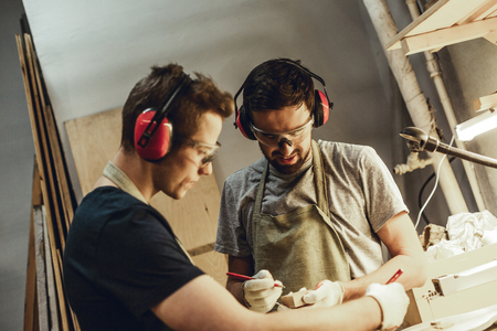 Two young handsome guys in earmuffs using pencils to make marks and draw sketch in professional workshop