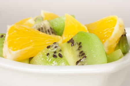 pieces of kiwi and oranges in white bowl photo
