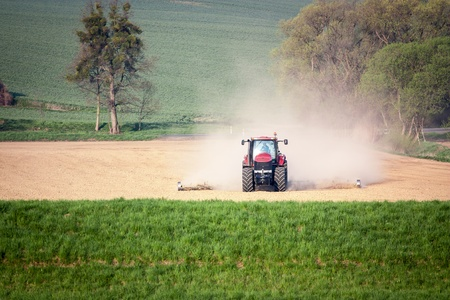 plough land: tractor in spring field work Stock Photo
