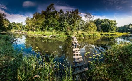 vlonder: landschap met een oude loopbrug, vijver en de blauwe hemel Stockfoto