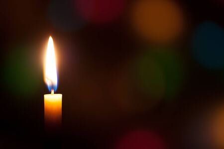 burning candle with a colored background photo