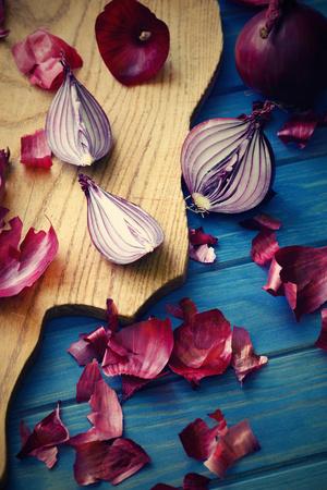 cebolla roja: cebolla roja partida en dos en un fondo de madera azul Foto de archivo