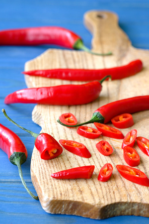 chopped red pepper on wooden plate Stock Photo