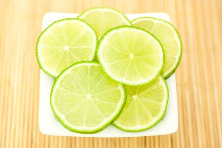 limes in a white bowl on a bamboo mat