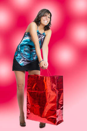 young woman gets up giant red bag, after Christmas shopping photo