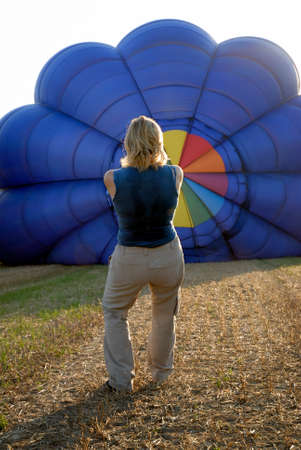 inflating: balloonist inflating her balloon Stock Photo