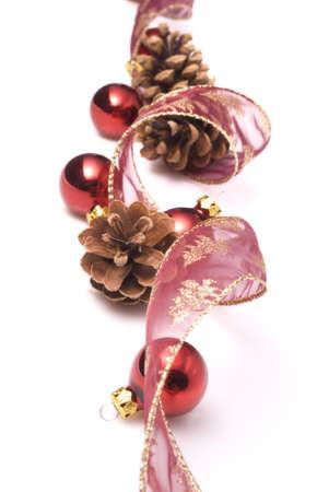 festones: adornos de navidad en fondo blanco, cinta, conos y bolas rojas