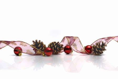 festoon: christmas decorations with ribbon, cones and red balls reflected on white background