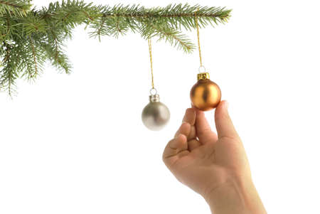 christmas tree and children hand hanging on a decorative ball photo