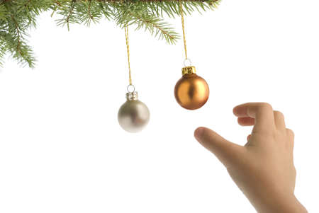 seizing: christmas tree branch with balls and children hand on white background