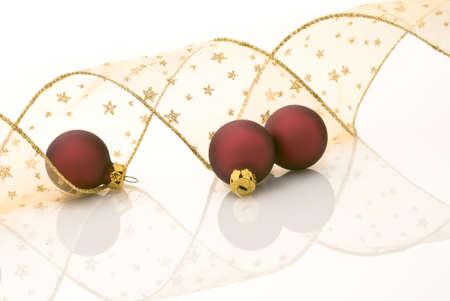 festoons: Satin red balls and golden ribbon decorated with stars on white background Stock Photo
