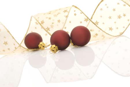 festones: Satin bolas rojas y doradas cinta con estrellas en fondo blanco  Foto de archivo