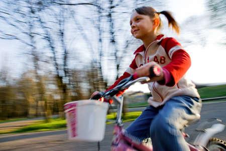 little girl biking in the park Stock Photo