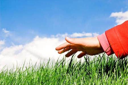 ni�os reciclando: mano sobre la hierba  Foto de archivo