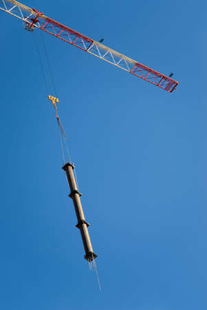 crane holding a prefabricated element against a limpid sky photo