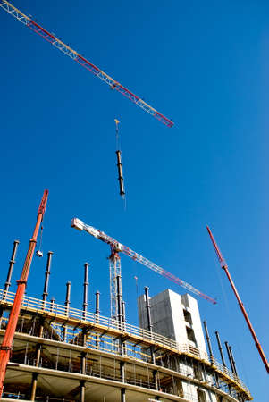 prefabricated: cranes in a building yard, one holding a prefabricated element against a limpid sky