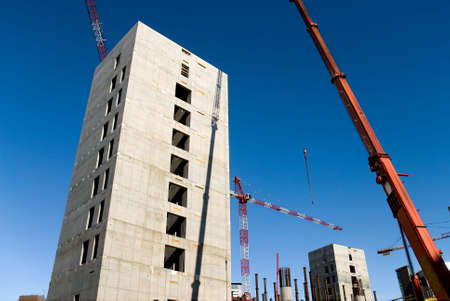 concrete structure and cranes against a limpid sky in a building yard photo