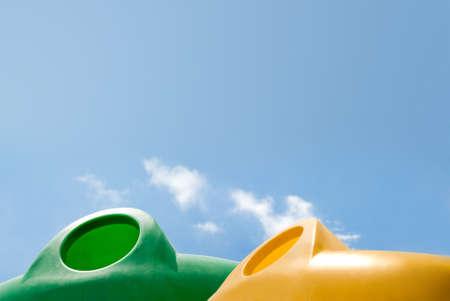 separacion de basura: Contenedores de basura contra un cielo azul sereno