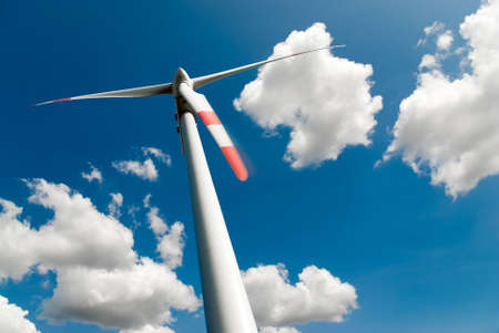 low angle view of a wind turbine against a blue sky full of white clouds photo