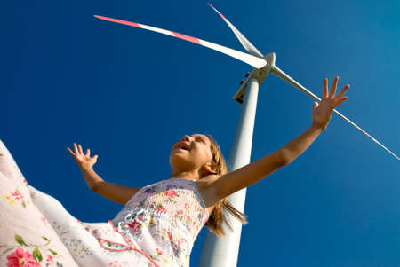 human energy: child playing with the wind near a wind turbine